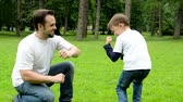 resist : middle aged father plays with son little boy - park Stock Footage