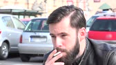 man elstv : Young handsome hipster man smokes a cigarette on the street - parked cars in the background