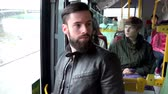 man elstv : PRAGUE, CZECH REPUBLIC - MAY 30, 2015: young handsome hipster man travel by bus with other people in background - urban street in the city