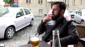 man elstv : Young handsome hipster man sitting in restaurant outdoor seating and smoking - street parked cars - beer