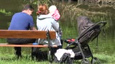 parent : PRAGUE, CZECH REPUBLIC - MAY 31, 2015: The family relaxing near pond - Mather and father with baby sit on bench - baby carriage - closeup