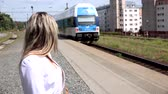 привод : young attractive blonde woman waits at railway station and woman watches trainset departing from the train station