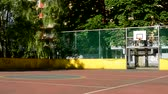 фехтование : focus on basketball playground surrounding by trees and prefab houses
