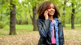 chatty : young african chatty smile girl talks with friend through the smartphone in the forest