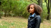 dodge : young beautiful african girl walks in the forest and observe the landscape - camera dodge the trees