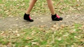 anlamlı : young african girl walks in the forest - camera focus her legs and shoes with significant pink laces Stok Video