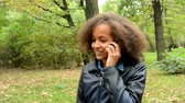 chatty : young charming talkative kind african woman walk in the forest and call with friend through smartphone - camera dodge trees Stock Footage