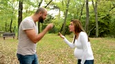 ököl : Young pretty pregnant woman and handsome man argue together in park - outdoor