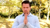 perceive : Young man stands in the woods and whith closed eyes prays.