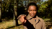 estréia : Young beautiful happy african girl stare into camera, emphatically shows forefinger ahead and stands in the woods - eye contact