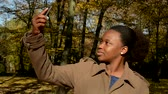 oneself : Young beautiful african happy girl stands in woods, poses and  makes selfie Stock Footage