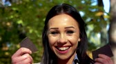 dark haired : Slowmotion young beautiful happy woman stands in park and breaks a bar of chocolate