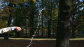 bastante : Slowmotion young beautiful woman stands in park and pours away water from glass Vídeos