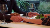 Male and female hands connected across a table with meal and wine