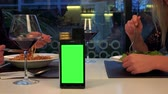 A man and a woman sit at a table and eat, a smartphone with a green screen in the foreground