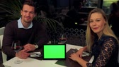 A man and a woman (both young and attractive) sit at a table in a restaurant and talk to the camera, a tablet with a green screen on the table