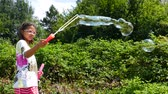 A little girl makes bubbles of soap foam. Stok Video