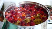 Boiling the pot with a plum compote. Abstract background, slow motion.
