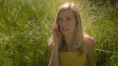 Portrait of a young blond caucasian woman sitting in the grass in the sunny outdoors talking on her cellphone. 4K slow motion Stok Video