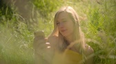 Peaceful young blond caucasian woman relaxing in the grass in the beautiful sunny looking at her Smart Phone. 4K Slow motion