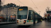 hodina : Time lapse of a Tramway line station in Paris France with crowds of busy stressed people commuting and moving fast, and two tram trains stopping on the railroads under a pink cloudy sky