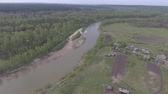 Panorama aerial view UHD shot on river, cottage village, in forest, suburb, village, above Стоковые видеозаписи