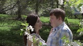 flirting : Loving couple walking in a park near a blossoming tree in the spring Stock Footage