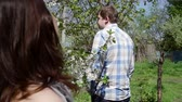 casual : man looks at a woman from a distance in the park in spring