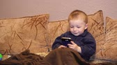 estragado : little boy plays game on a smartphone