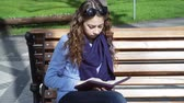 campus : young woman sits on a bench in the Park and reading book