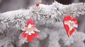 bead : red Wooden Christmas toys heart and fir-tree hanging on the branches of the snowly Christmas tree. video motion hd Stock Footage