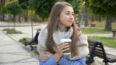 Close-up of the face of woman who drinks hot tea or coffee in autumn park, she wears knitted scarf. girl drinks coffee for good mood from mug Stock Footage