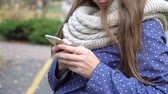 Caucasian woman with knitten scarf using smart phone, typing something during walking in autumn park. video 4k Stock Footage