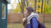 Beautiful young woman wears knitted scarf and walking in autumn park. 4k video motion Stock Footage