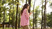 Beautiful girl is walking in city park and using smartphone, young woman is holding device and touching screen, summer nature is visible Stock Footage