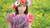 Woman with wreath on head picks lilac and tulip flowers in garden. Happy woman gardener with flowers. Spring and summer. I love to work with plants