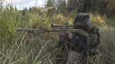 troops : Sniper rifle in protective suit sitting in a field Stock Footage