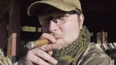 recon : Military smoking a cigar near a building Stock Footage
