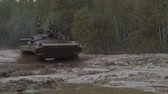 combativo : Military armored personnel carrier travels along the muddy road. Dirty armored vehicle