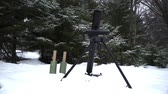 serviceman : Mortar is charged and ready to fire in the winter forest
