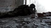 haki : Military man with arms lies in ambush in an abandoned building Stok Video