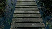 bridge across the river : Wooden bridge over river. Walking on a wooden bridge across river. Stock Footage