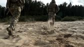 конфликт : Military soldiers with weapons running on sand back view. Military man