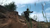 troops : Soldiers with military weapons jumping down from sand hill in quarry Stock Footage