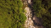 wood : Drone view wooden bridge over rocky river in mountain. Mountain river with large stones and green forest aerial landscape.