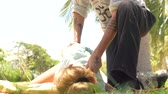 receive : Woman receiving acupuncture massage. Massagiste doing yoga massage outdoor. Professional acupressure massage. Relaxation and rehabilitation concept.