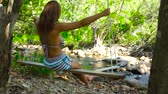 human back : Happy woman in bikini on swing in rainforest on river shore back view. Young woman swinging on swing in jungle forest. Stony river on background.