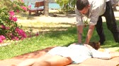 реабилитация : Man massagiste making thai massage to woman outdoor. Professional acupuncture massage for healing and rehabilitation body. Alternative and traditional medicine concept. Стоковые видеозаписи