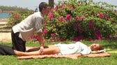 acupuncture : Man doing yoga massage to woman outdoor. Man massagist making thai massage to woman lying on grass. Traditional indian massage for harmony and relaxation. Healty lifestyle concept.
