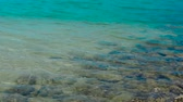 sandy bottom : Water surface and ripple waves in tranquil sea with stones on sandy bottom. Blue water in calm sea and rocky bottom on summer beach.